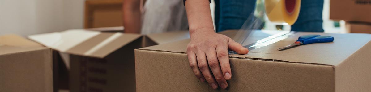 Frau klebt Umzugsbox zu als Symbol für Umzugsunternehmen Kornwestheim