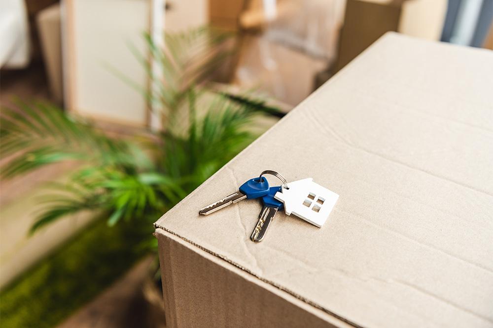Hausschlüssel liegt auf gepacktem Umzugskarton für Umzug ins Ausland.