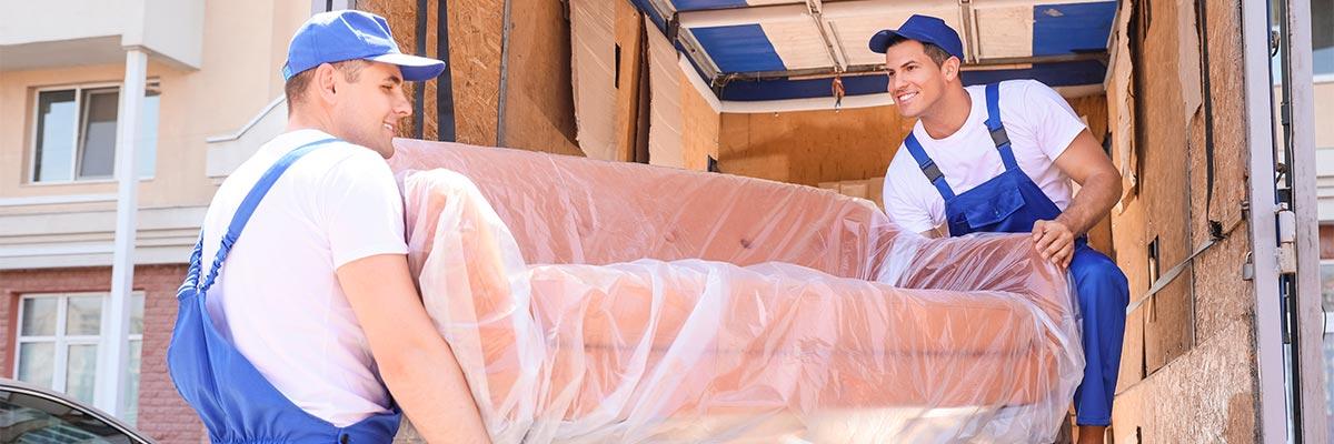 Handwerker tragen Sofa in Umzugsauto als Symbol für sicheren Sofa-Transport