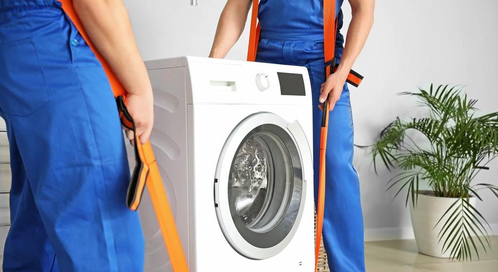 Umzugshelfer transportieren sicher eine Waschmaschine
