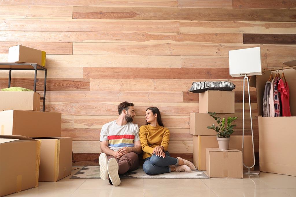 Paar sitzt neben Umzugskartons