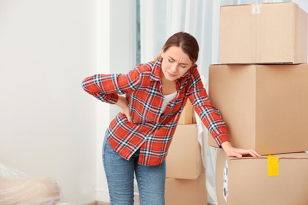 Frau hält sich den Rücken wegen Schmerzen durch Kartons heben